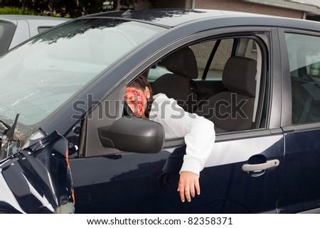 Bleeding woman driver unconscious after a car crash - stock photo