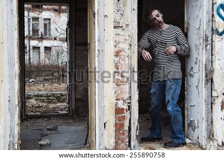 Bleeding young man with white spooky eyes - stock photo