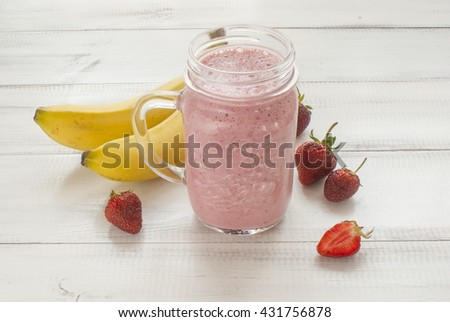 Blended banana strawberry smoothie on white wooden background