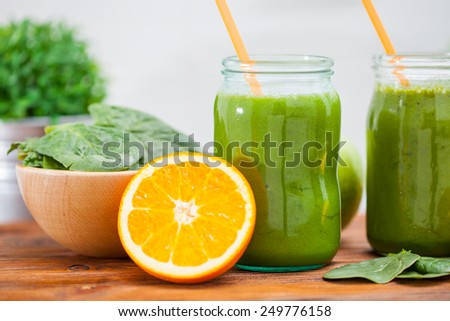 Blended green smoothie with ingredients selective focus square image - stock photo