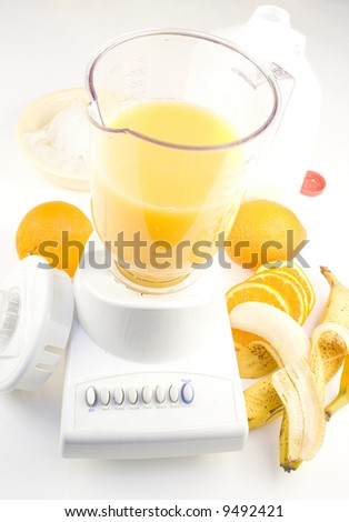 Blender with fruit, ice and milk to make smoothies - stock photo