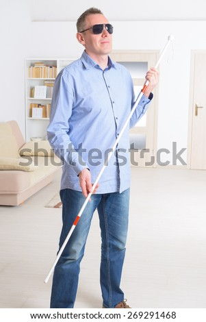 Blind man with white stick and dark glasses at home - stock photo