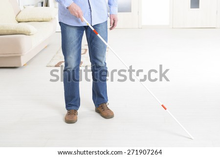 Blind man with white stick at home - stock photo