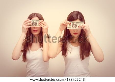 blind money concept: 2 beautiful girls young women wearing white shirts covering eyes with USD dollar banknote on white copy space background portrait - stock photo