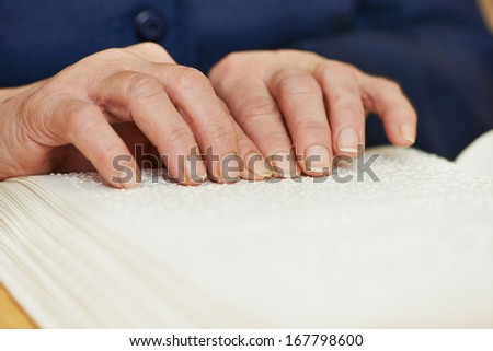 Blind or visually handicapped woman hands reading book written in Braille - stock photo