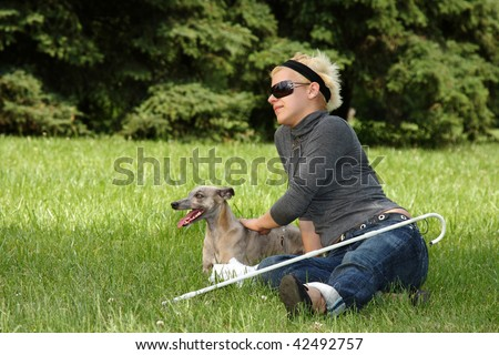 blind woman with her little dog in a park - stock photo