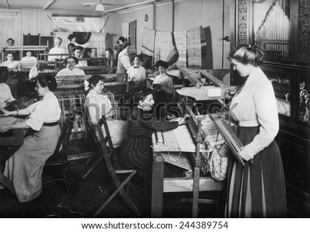 Blind women weaving at looms accompanied by an orchestrion, a self playing musical instrument, at right. Photo taken by Byron Company for the New York Association for the Blind. - stock photo