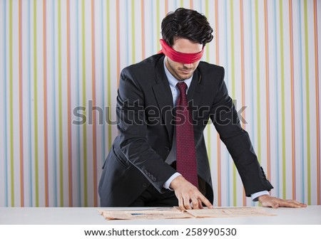 Blindfold businessman reading the newspaper - stock photo