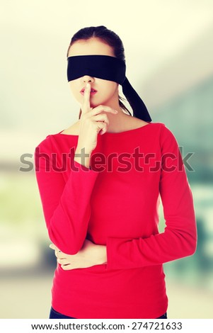 Blindfold woman with finger on lips