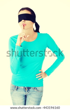 Blindfold woman with finger on lips. - stock photo
