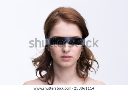Blindfold young woman over gray background - stock photo