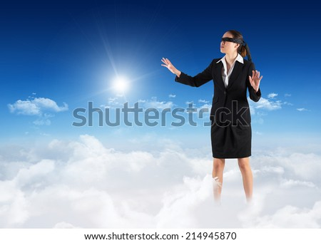 Blindfolded businesswoman with hands out against bright blue sky over clouds