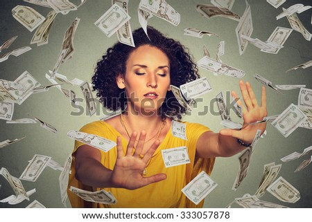 Blindfolded young entrepreneur businesswoman with closed eyes trying to catch dollar bills banknotes flying in the air on gray wall background. Financial corporate success or crisis challenge concept - stock photo