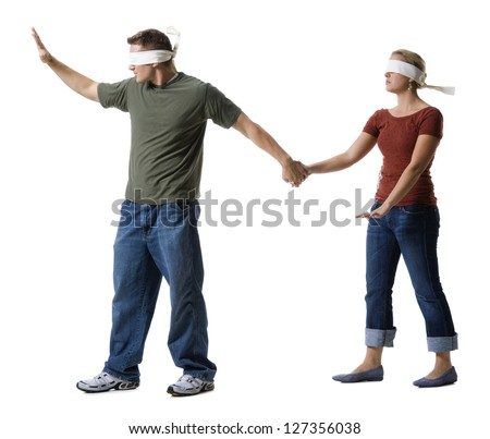 Blindfolded young man leading to a blindfolded young woman - stock photo