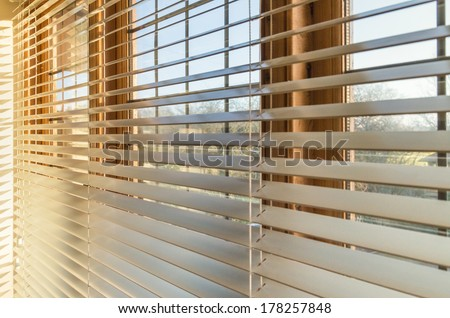 Blinds in a home catching the sunlight - stock photo