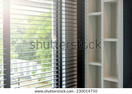 blinds inside a window being opened with bedroom interior - stock photo