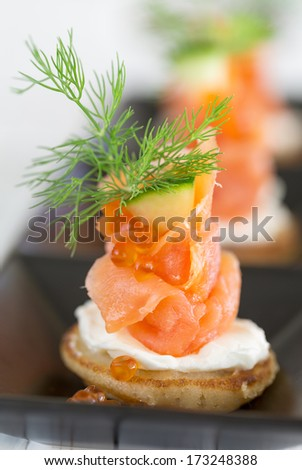 Blini with smoked salmon and sour cream, garnished with dill and caviar. Close-up view - stock photo