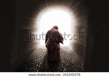 blissed Friar with faith on god walking toward the light - stock photo