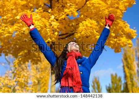 Blissful excited woman raising arms to golden yellow trees and praising on autumn day in park or forest. Caucasian fun girl happiness on fall season. - stock photo