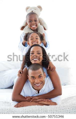 Blissful family having fun lying down on bed at home