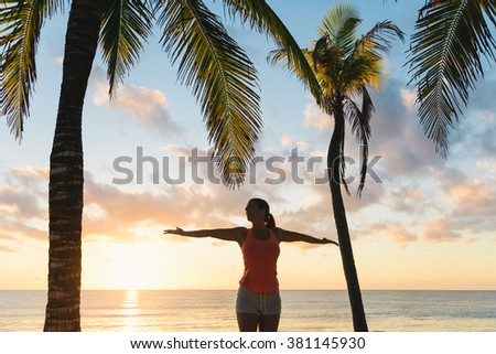 Blissful fitness woman enjoying outdoor summer sunrise or sunset workout at the beach. Happy female athlete exercising during vacation under tropical palms at Riviera Maya, Mexico.