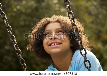 blissful girl on a swing in the park - stock photo