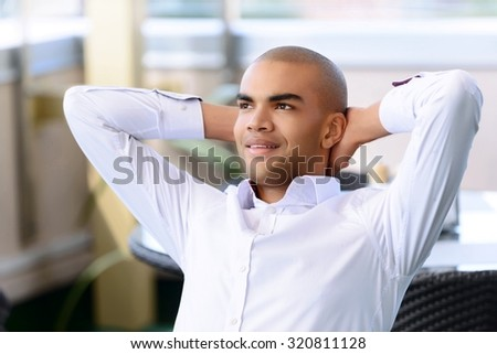 Blissful moment. Cheerful delighted handsome man holding his hands folded behind the head and sitting while expressing gladness - stock photo
