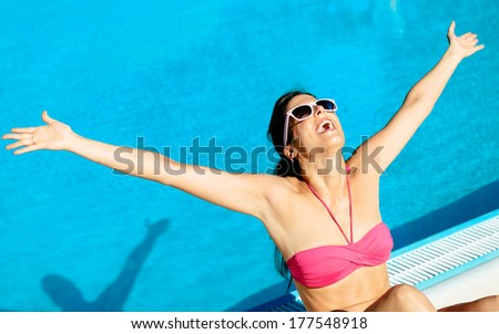 Blissful woman having fun at swimming pool on summer vacation. Successful happy girl raising arms at poolside. - stock photo