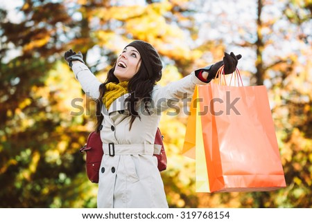 Blissful woman holding shopping bags and having fun buying in autumn rain. Successful female shopper outside in fall season. - stock photo