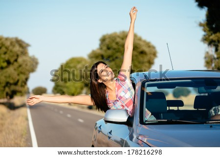 Blissful woman on car travel raising arms. Happy brunette girl enjoying freedom on roadtrip vacation. - stock photo