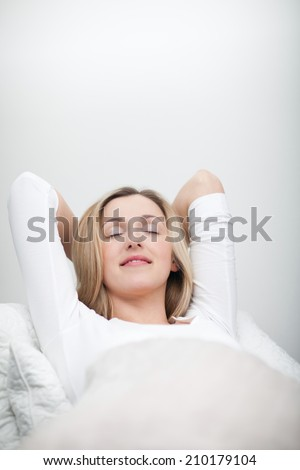 Blissful young woman relaxing in bed stretched out on her back with her hands behind her head and a beautiful smile of satisfaction