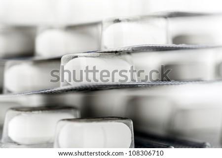 Blister packs of white pills. Shallow DOF. - stock photo
