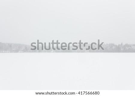 Blizzard winter landscape at frozen lake - stock photo