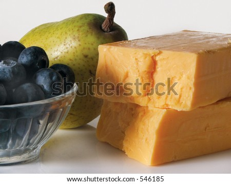 Block of cheddar with fruit. - stock photo