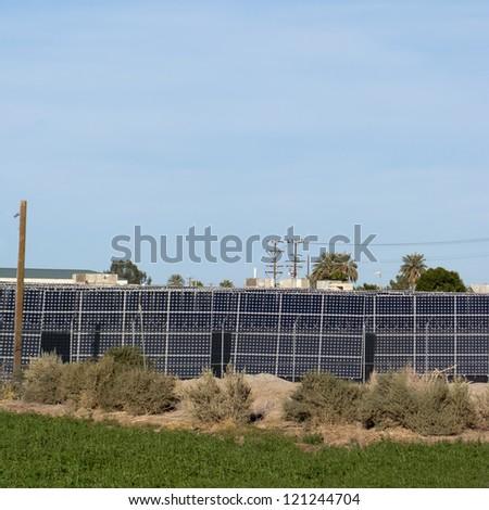Block of electric solar panels installed at backyard perimeter - stock photo