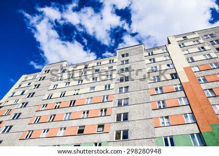 Block of flats high in the blue sky. - stock photo