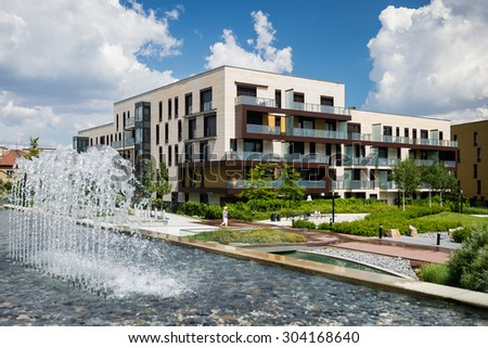 Block of flats in green public park with water steam during hot summer day - stock photo
