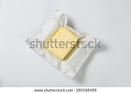 block of fresh butter on white background - stock photo