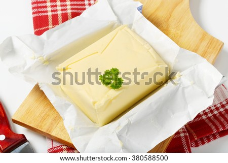 block of fresh butter on wooden cutting board - close up - stock photo