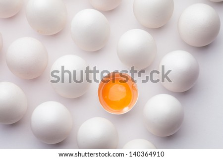 Block of sixteen eggs; fifteen are undisturbed, the last is halved with the yolk sitting the shell.  Shot from above on white background. - stock photo