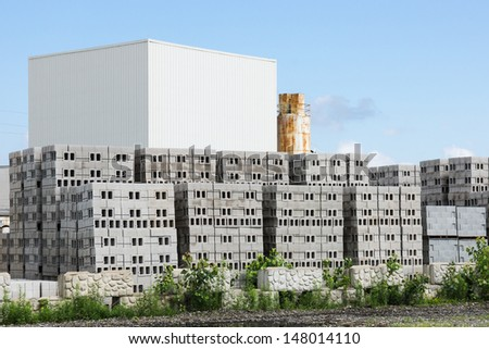 Block Plant:  Stacks of unsold concrete blocks sit in front of a block making plant - stock photo