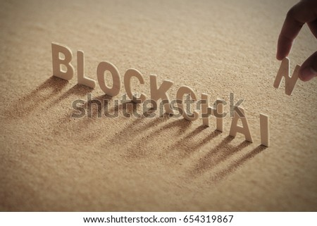BLOCKCHAIN wood word on compressed or corkboard with human's finger at T letter.