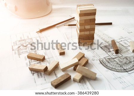 Blocks wood game (jenga) on blueprint or architectural project. - stock photo