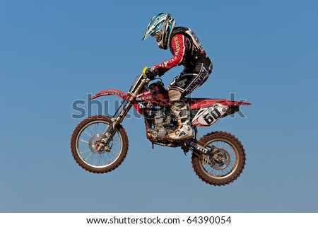 BLOEMFONTEIN, SOUTH AFRICA - JULY 19: Unidentified motocross rider jumps through the air during a national motocross racing event, on Jul 19, 2009 in Bloemfontein, South Africa. - stock photo