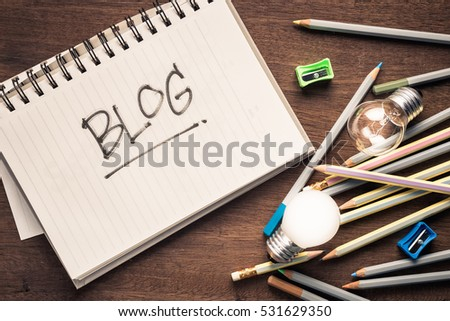Blog text on notebook with writing equipment and light bulbs as symbol of creative idea