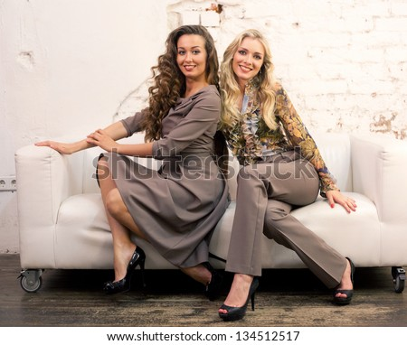 blond and brown model sitting on the sofa laughing