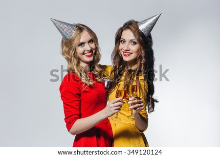 Blond and brunette beautiful smiling girls in holiday hats are celebrating christmas and new year with the glasses of drink on white isolated background. Party concept - stock photo