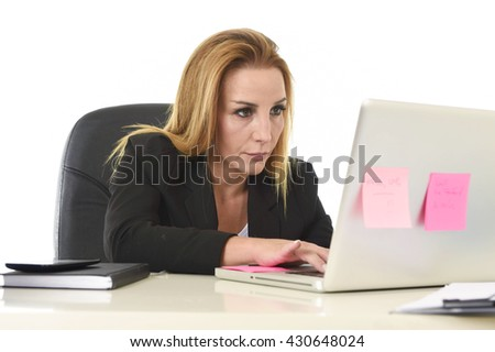 blond attractive 40s woman in business suit working at laptop computer in office desk looking focused and concentrated typing in busy and successful businesswoman concept - stock photo