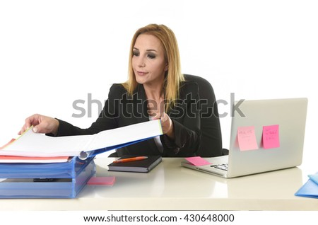 blond attractive 40s woman in business suit working with folders paperwork and laptop computer in office desk looking focused and concentrated in busy and successful businesswoman concept - stock photo