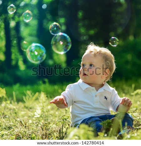 Blond baby boy dressed in white shirt and blue jeans sitting on grass and playing with soap bubbles in park